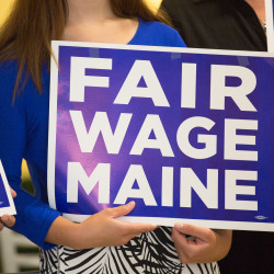 Supporters of a referendum to increase Maine's minimum wage to $12 per hour by 2020 hold signs at a press conference at Fork and Spoon in Bangor in this June 2016 file photo.